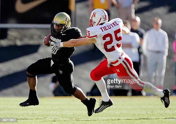 Free safety Blake Tiedtke of the Nebraska Cornhuskers corrals tailback Hugh Charles of the Colorado Buffaloes in the first quarter on November 25...