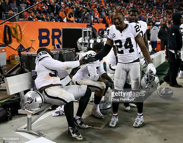 Free safety Charles Woodson and defensive end Benson Mayowa of the Oakland Raiders celebrate as a game against the Denver Broncos ended with a 15-12...