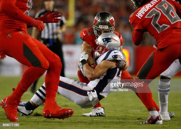 Free safety Chris Conte of the Tampa Bay Buccaneers tackles wide receiver Danny Amendola of the New England Patriots during the second quarter of an...
