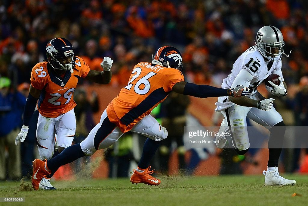 Free safety Darian Stewart #26 of the Denver Broncos tackles wide receiver Michael Crabtree #15 of the Oakland Raiders in the fourth quarter of the game at Sports Authority Field at Mile High on January 1, 2017 in Denver, Colorado.
