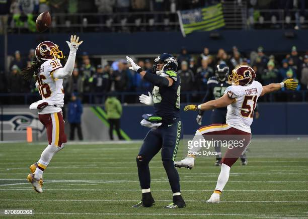 Free safety D.J. Swearinger and inside linebacker Will Compton of the Washington Redskins break up a pass intedned for tight end Jimmy Graham of the...