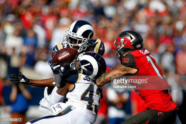 Free safety Eric Weddle and strong safety John Johnson of the Los Angeles Rams break up a pass intended for wide receiver Mike Evans of the Tampa Bay...