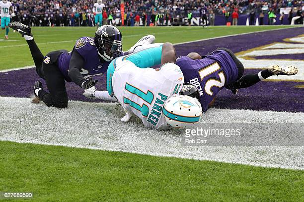 Free safety Lardarius Webb of the Baltimore Ravens intercepts the ball against wide receiver DeVante Parker of the Miami Dolphins in the second...