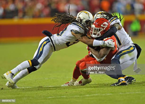 Free safety Tre Boston and strong safety Jahleel Addae of the Los Angeles Chargers tackle running back Kareem Hunt of the Kansas City Chiefs during...