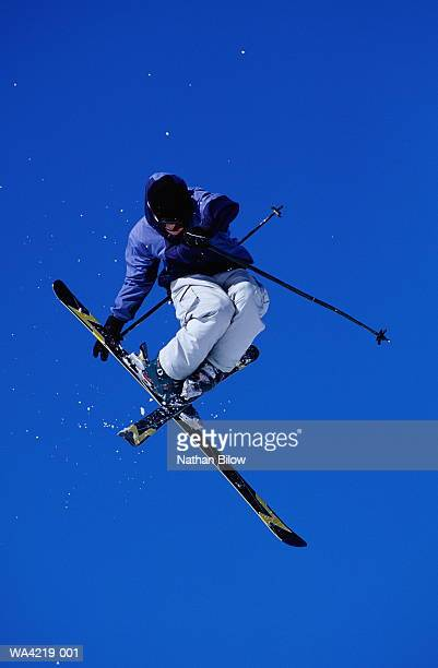 free skier in mid-air jump, low angle view - フリースタイルスキー ストックフォトと画像
