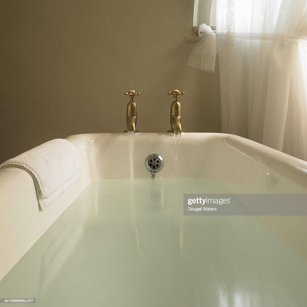 Free standing bath with taps running : ストックフォト