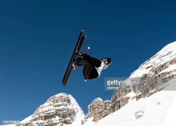 free style skier practicing big air against mountains - winter sports event stock pictures, royalty-free photos & images