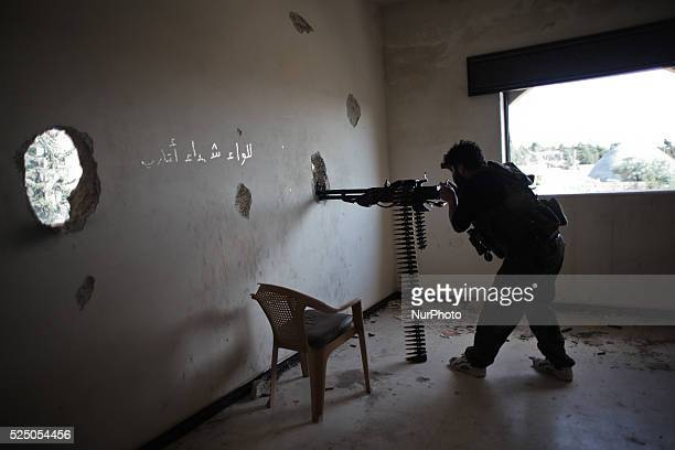 A Free Syrian Army fighter fires his heavy weapon during clashes with forces loyal to Syria's President Bashar alAssad in the Khan alAssal town for...