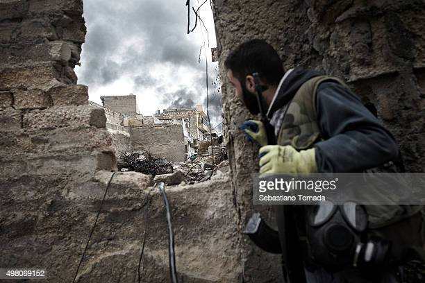 Free Syrian Army fighter observes the damage and smoke rising from a civilian neighborhood after being targeted by a Syrian Army artillery strike....