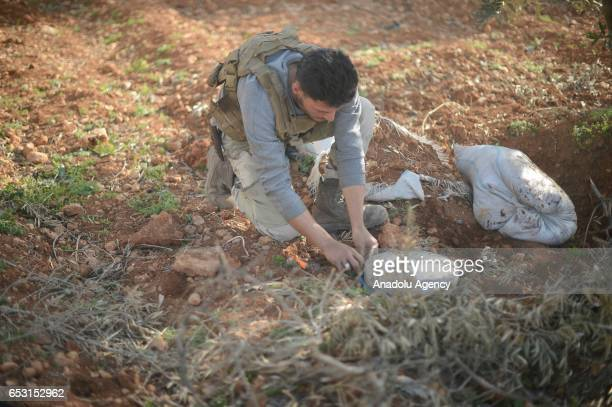 Free Syrian Army member defuses mines placed in the farms by Daesh terrorist as soldiers continue to clean the alBab town of Aleppo from Daesh during...