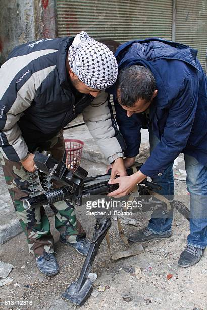 Free Syrian Army members inspect a grenade launcher in Karmal AL Jabal It is estimated that 400000 people have died in the past 5 years during the...