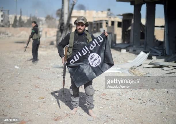 Free Syrian Army members remove Daesh flags as they move forward to the center of AlBab district during the 'Operation Euphrates Shield' in Aleppo...