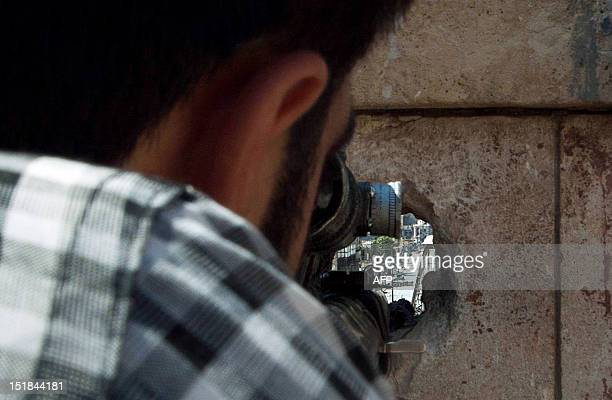 Free Syrian Army sniper takes aim at an army position in Aleppo's old city on September 10 2012 FSA snipers take position on rooftops of Aleppo's old...