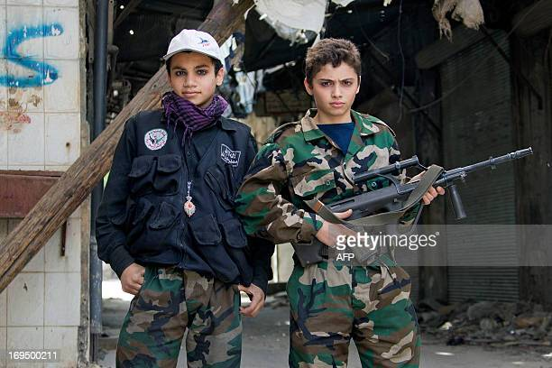 Free Syrian army's young fighters pose on April 2 2013 as they hold positions near the front line during clashes with regime froces in the old city...