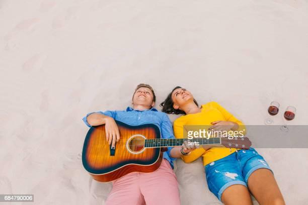 Gratuit jeune couple allongé sur la plage de sable
