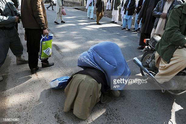 A freed Afghan prisoner kisses his mother's feet following his release from prison in Herat on November 6 2012 Sixty three prisoners including six...