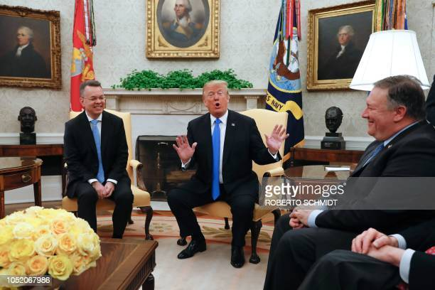 Freed American pastor Andrew Brunson smiles as he listens to US President Donald Trump flanked by US Secretary of State Mike Pompeo during a meeting...