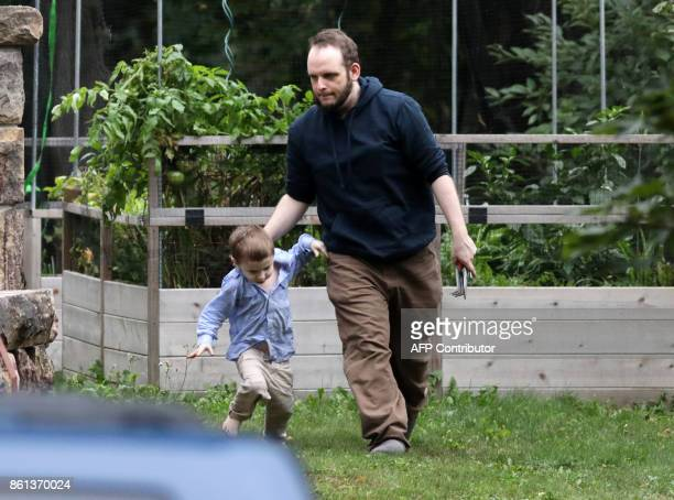 Freed Canadian hostage Joshua Boyle and one of his children walk outside the Boyle's family home in Smiths Falls Ontario Canada on October 14 2017...