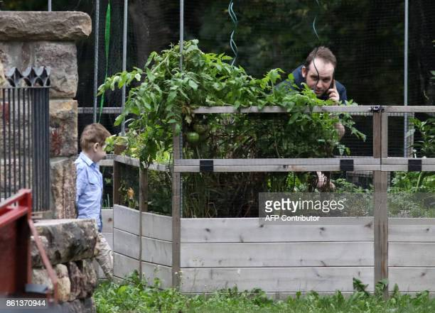 Freed Canadian hostage Joshua Boyle talks on the phone as one of his children plays outside the Boyle's family home in Smiths Falls Ontario Canada on...