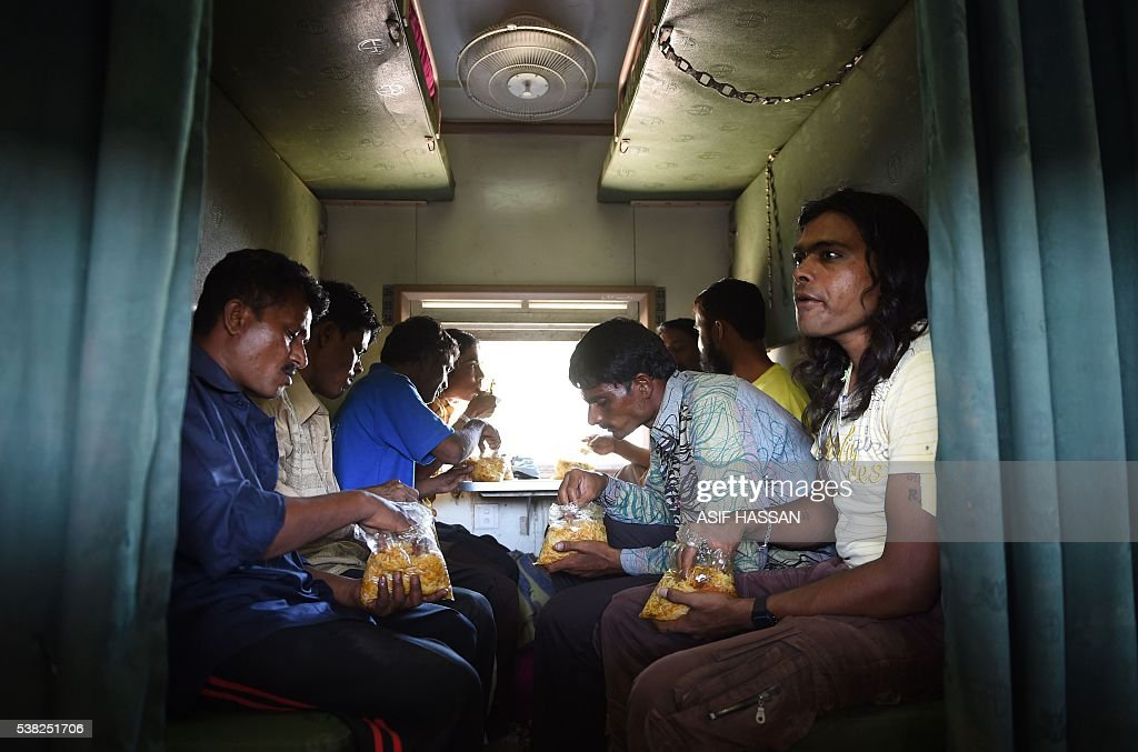 Freed Indian fishermen eat rice distributed by volunteers from Pakistani charity Edhi while they sit in the carriage of a train at a railway station..