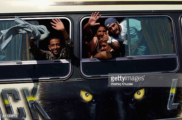 Freed Iraqi Prisoners guarded by two US Army vehicles wave to their relatives from inside a bus as they leave the Abu Gharib prison compound August 1...