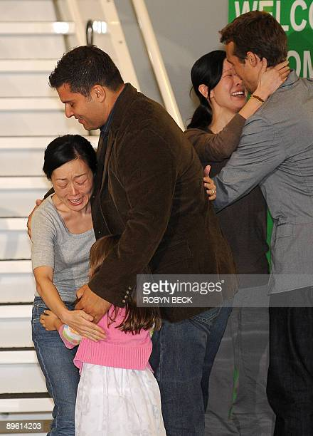 Freed US journalist Euna Lee embraces her husband Michael Saldate and daughter Hana and fellow journalist Laura Ling embraces her husband Iain...