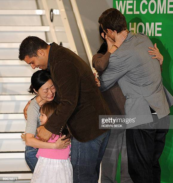 Freed US journalist Euna Lee embraces her husband Michael Saldate and daughter Hana and US journalist Laura Ling embraces her husband Iain Clayton...