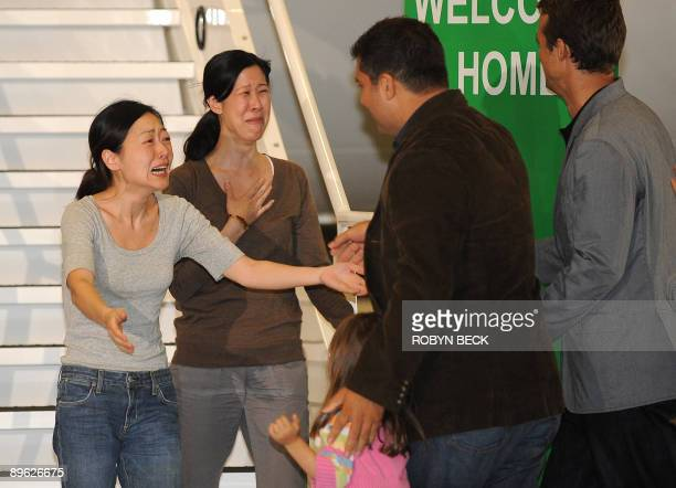 Freed US journalist Euna Lee embraces her husband Michael Saldate and daughter Hana while fellow journalist Laura Ling ) embraces her husband Iain...