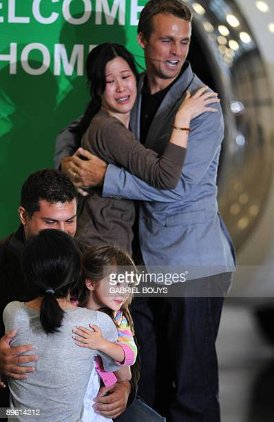 Freed US journalists Laura Ling embraces her husband Iain Clayton, while Euna Lee is welcomed by husband Michael Soldate and daughter Hana after they...