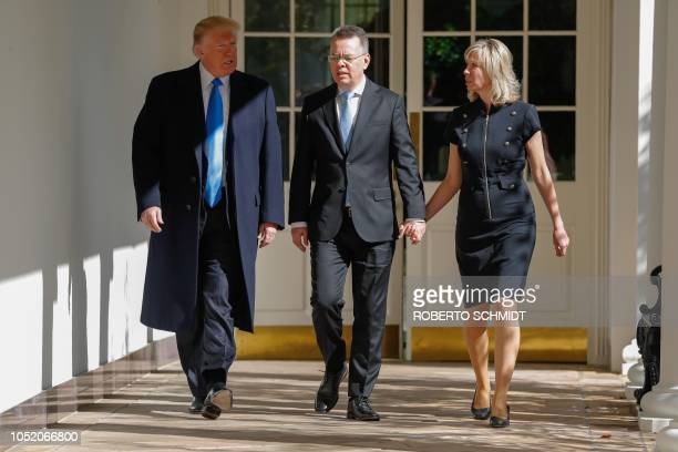 Freed US pastor Andrew Brunson and his wife walk with US President Donald Trump before a meeting in the Oval Office at the White House in Washington...