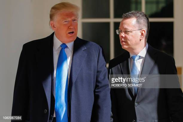 Freed US pastor Andrew Brunson looks at US President Donald Trump before a meeting in the Oval Office at the White House in Washington DC October 13...