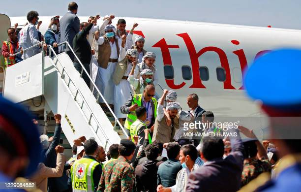 Freed Yemeni Huthi prisoners wave to the crowd as they descend the stairs of the plane that transported them on Ocotber 15, 2020 to Sanaa airport,...