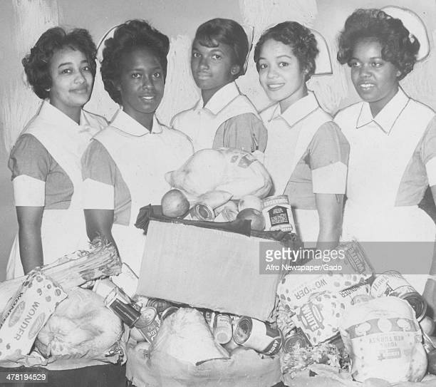 Freedmen's School of Nursing students give baskets to a needy family, Washington DC, December 29, 1967. Pictured are, from left, Miss Carolyn...