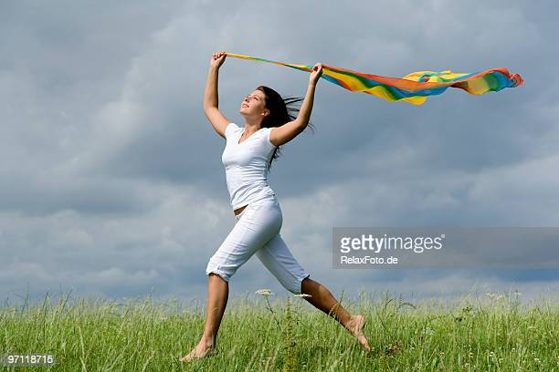 Freedom and fun - Happy young woman running over meadow