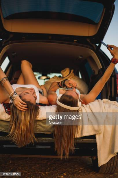 freedom and relaxation in the car trunk for a couple of female friends - straight hair stock pictures, royalty-free photos & images