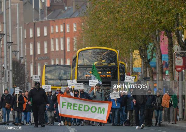 Freedom Health Ireland protesters carry 'Freedom' banner on O'Connell Street during an anti-lockdown protest, as they walk to join the Irish Freedom...