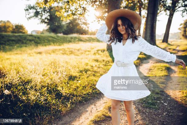 freedom is in the air, young female wearing bracelet white dress and straw hat enjoys her freedom. - white dress stock pictures, royalty-free photos & images