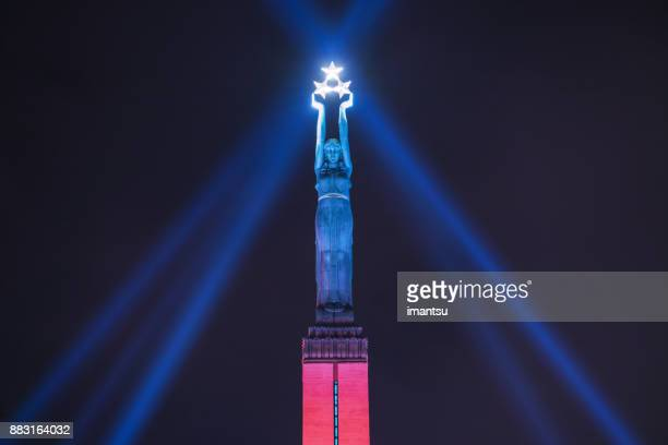 """freedom monument of latvia in the nighttime amidst the festival """"staro riga"""" - in two colors - monument stock pictures, royalty-free photos & images"""