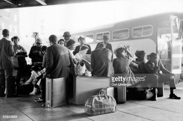 Freedom Riders sit on their luggage at a bus station Birmingham Alabama May 1961 As part of a protest against the racial segregation of passengers on...