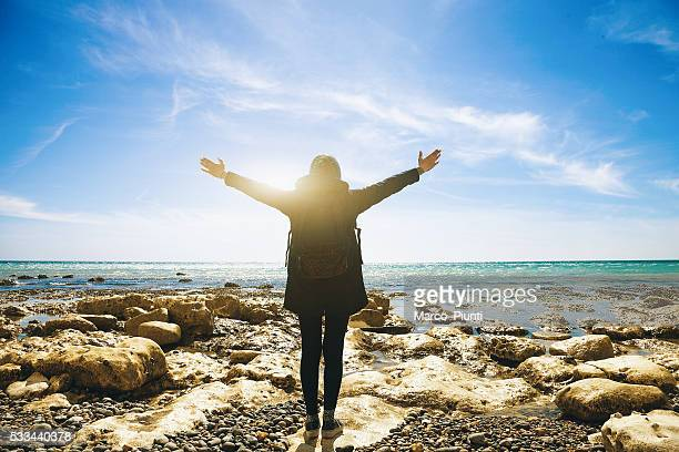 Freedom-Woman arms outstretched by the sea
