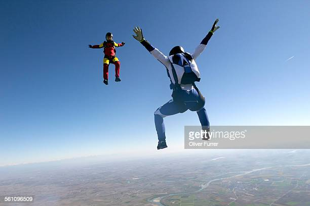 freeflying skydivers in blue sky - woman straddling man stock pictures, royalty-free photos & images