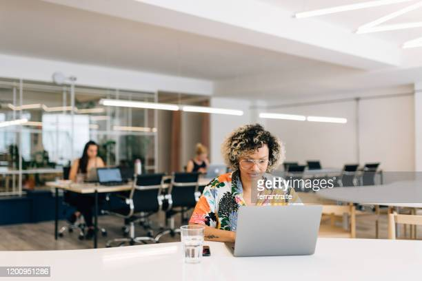 femme d'affaires freelance travaillant dans le bureau de coworking - hot desking photos et images de collection