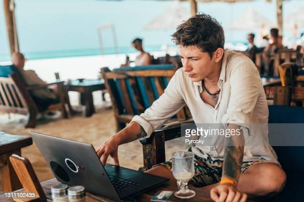 ein freiberuflicher mann arbeitet online in einem café am strand - minderheit stock-fotos und bilder