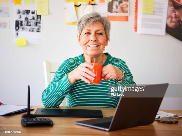 freelance senior woman working at home - rich_legg stock pictures, royalty-free photos & images
