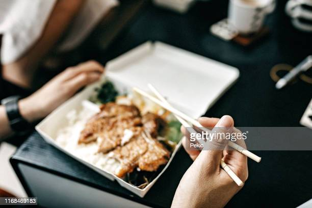freelancer having delivery food for lunch - chinese takeout stock pictures, royalty-free photos & images