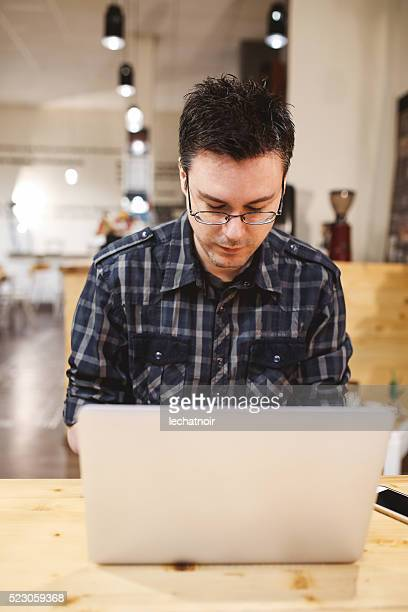 Freelancer man designer with a laptop in a cafe