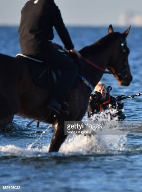 Freelancer photographer Sharon Chapman is a caught out by the tide as Winx walks through the water at Altona Beach during a recovery session on...