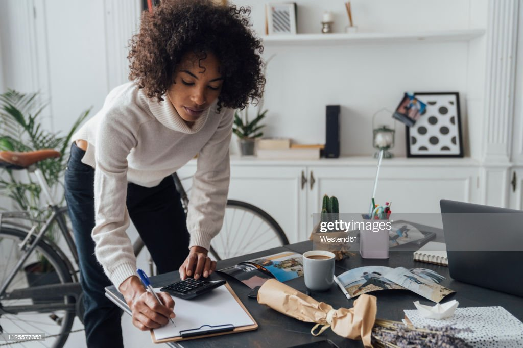 Freelancer standing at hert desk, using calculater, taking notes : Stock Photo