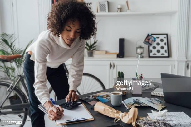 freelancer standing at hert desk, using calculater, taking notes - rechnungswesen stock-fotos und bilder