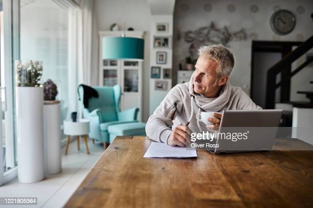freelancer using laptop and taking notes at table in home office - seitenblick stock-fotos und bilder
